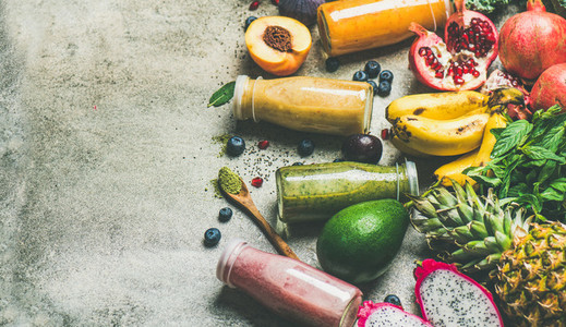 Colorful smoothies in bottles with fresh fruit  copy space