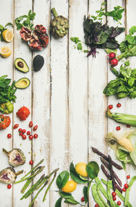 Healthy raw summer vegan ingredients over wooden background