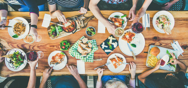 eating and leisure concept   group of people having dinner at table with food