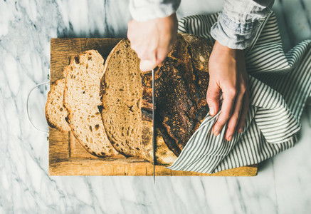 Female hands cutting freshly baked sourdough bread into pieces