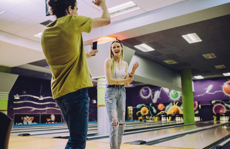 Friends enjoying playing at bowling arena