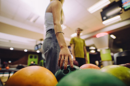 Woman choose ball for bowling game