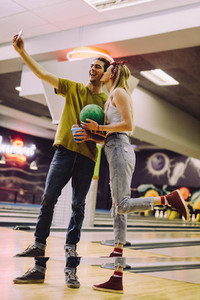 Couple taking selfie of at bowling club