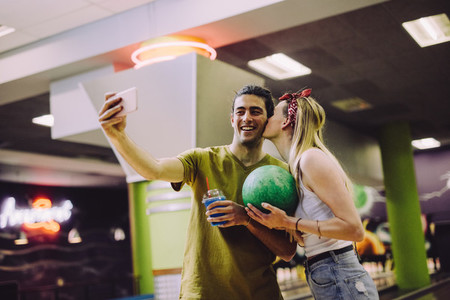 Loving couple taking selfie at bowling arena
