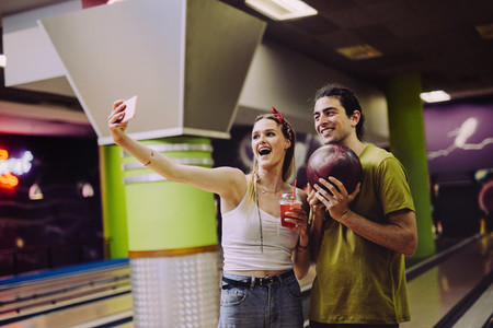 Couple taking selfie at bowling alley