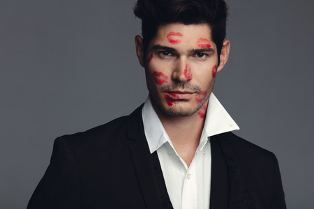 Attractive man with lipstick marks on face