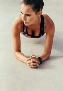 Muscular young woman doing plank exercise