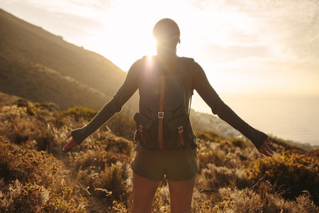 Female hiker embracing the sun light