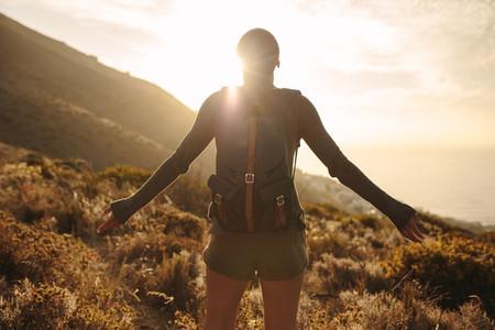 Female hiker embracing the sun light