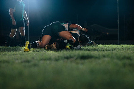 Rugby players striving for ball on sports arena