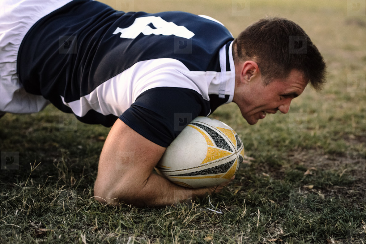 Strong rugby player with ball on ground