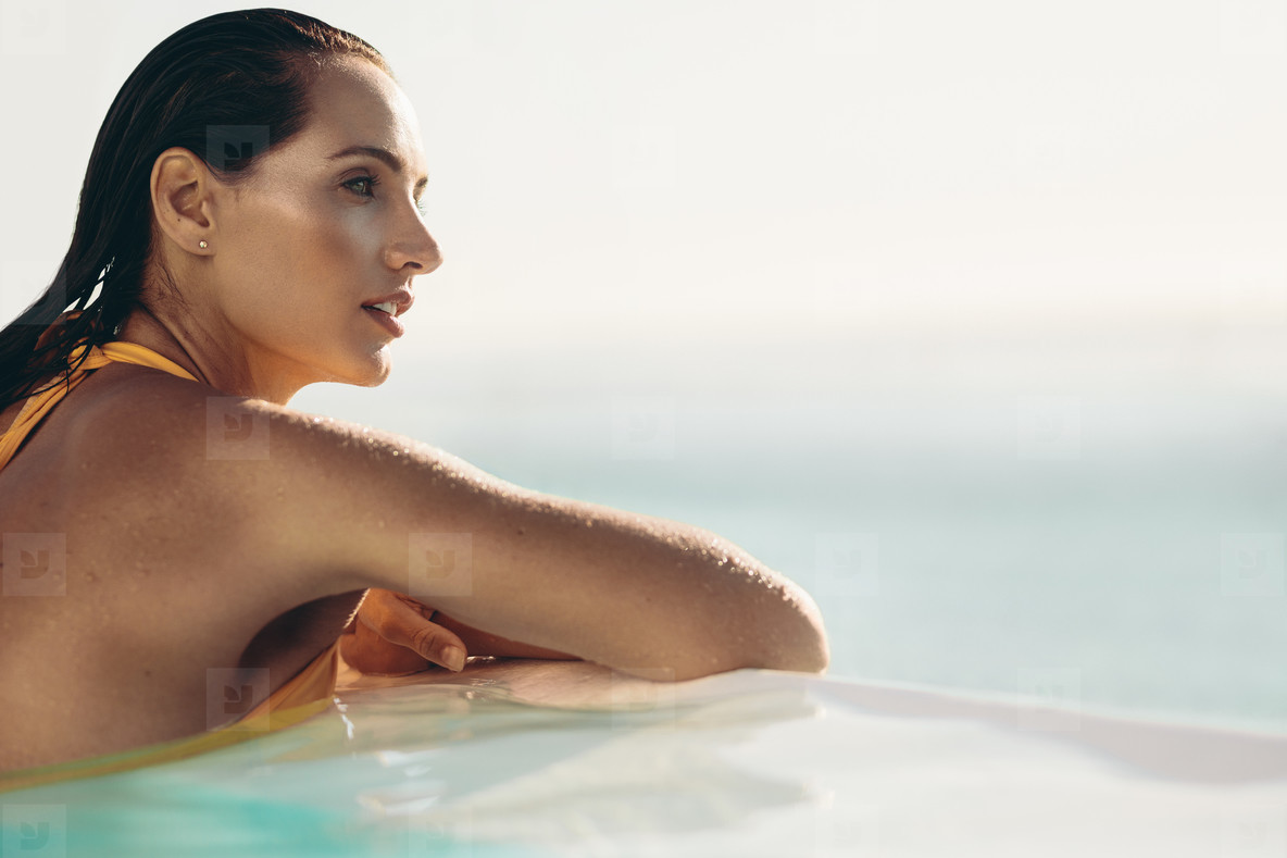 d53c39b0698 Photos - Attractive woman relaxing in infinity pool - YouWorkForThem