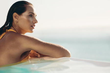 Attractive woman relaxing in infinity pool