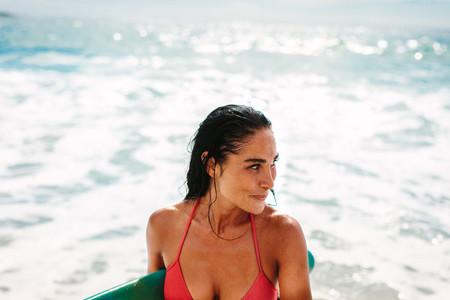 Beautiful female surfer at the sea