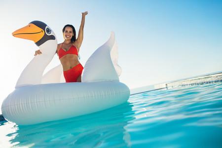 Woman having fun on a giant inflatable swan in pool