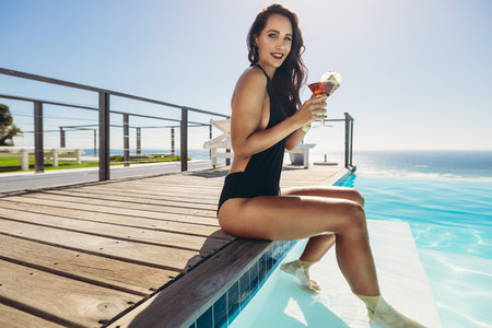 Woman with cocktail relaxing by the pool
