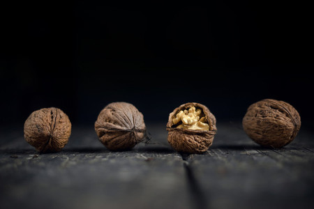 Walnuts on a grey textured wooden table  Assortment of nuts isolated on rustic old wooden background and splintered walnut with heart shaped core  Walnuts close up