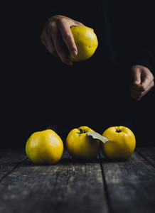 Quince in hand and on dark wooden background Autumn fruits