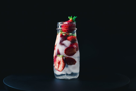 strawberry infused water with ice on a black background