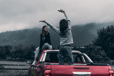 two girls sitting on the car and enjoy the view of the mountains and drink coffee Concept Travel