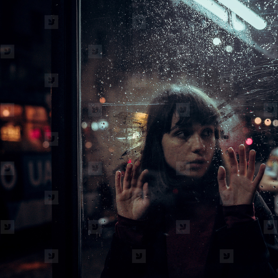 sad girl behind rain glass on night city background