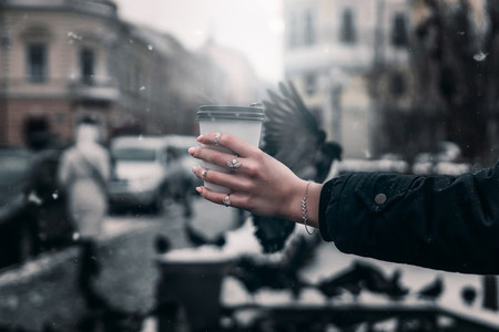 A girls hand with decorations holds a mug of coffee on a gray s
