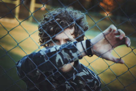curly haired boy in camouflage shirt  hiding his face with his hand behind the net