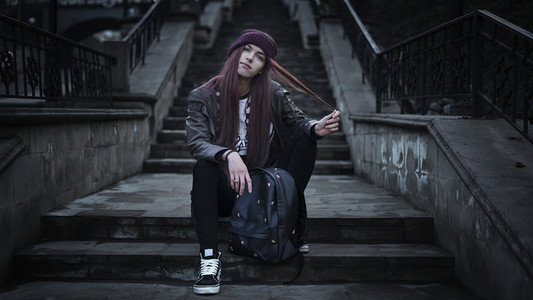 A girl in a purple hat sits on the steps