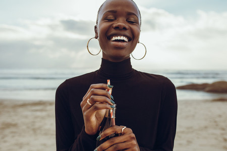 Woman smiling with cola at the beach