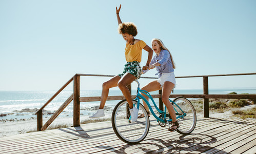 Female friends having fun on a bike at beach