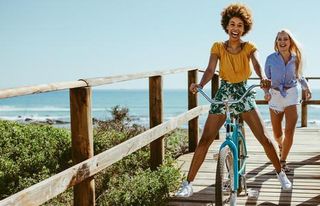 Girls having fun with bike on boardwalk