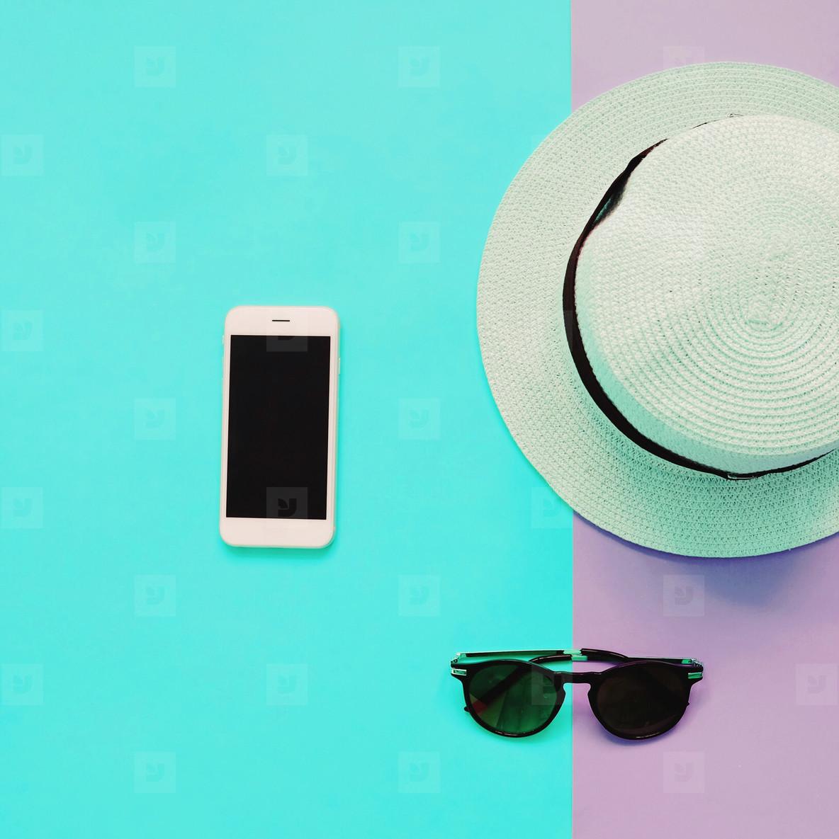 Flat lay fashion of smart phone  panama hat and sunglasses
