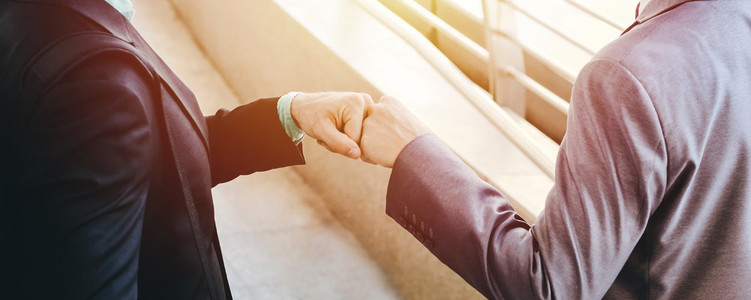 Two businessmen make fist bump on the public