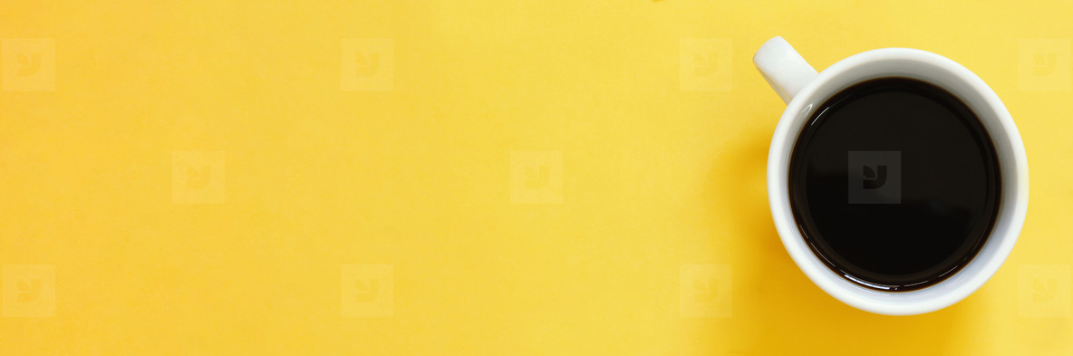 Top view of black coffee cup on yellow background
