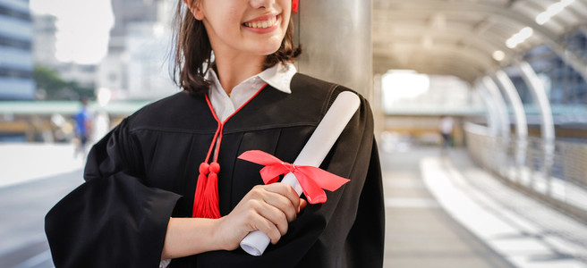 Young student woman smiling and holding diploma certificate