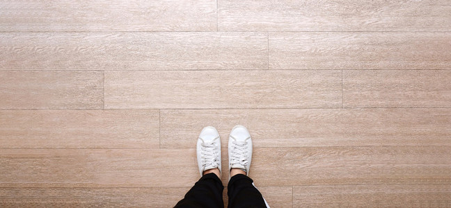 Selfie of feet in fashion sneakers on wooden floor background