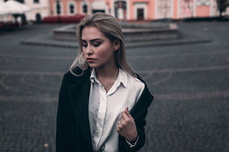 Beautiful blonde young woman in nice black coat  Posing on old c