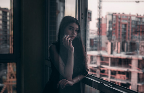 beautiful girl smokes near the window