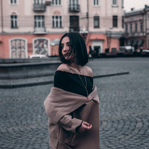 cute brunette in a coat walks around the city