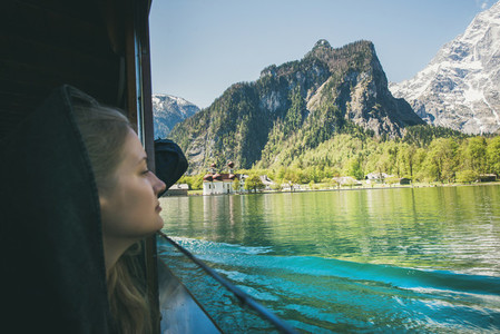 Young woman traveler looking out of window on boat trip at Konigsee Lake in berchtesgaden in Bavaria  Germany