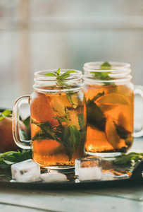 Summer refreshing cold peach ice tea on tray vertical composition