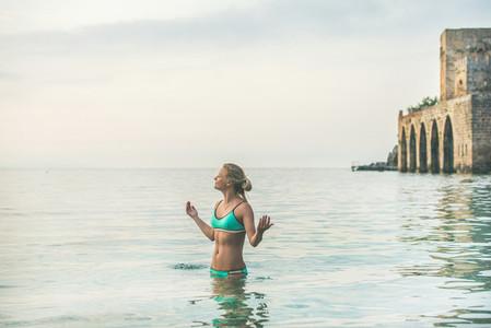 Young woman in blue bikini relaxing in sea in Alanya