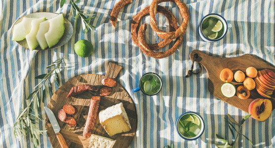 Picnic set with fruit cheese toast honey wine with a wicker basket and a blanket Beautiful summer background with girl and products on nature