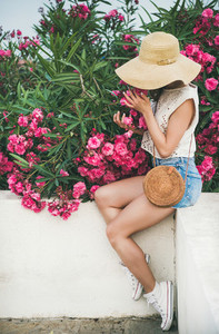 Young blonde woman smelling blooming oleander tree