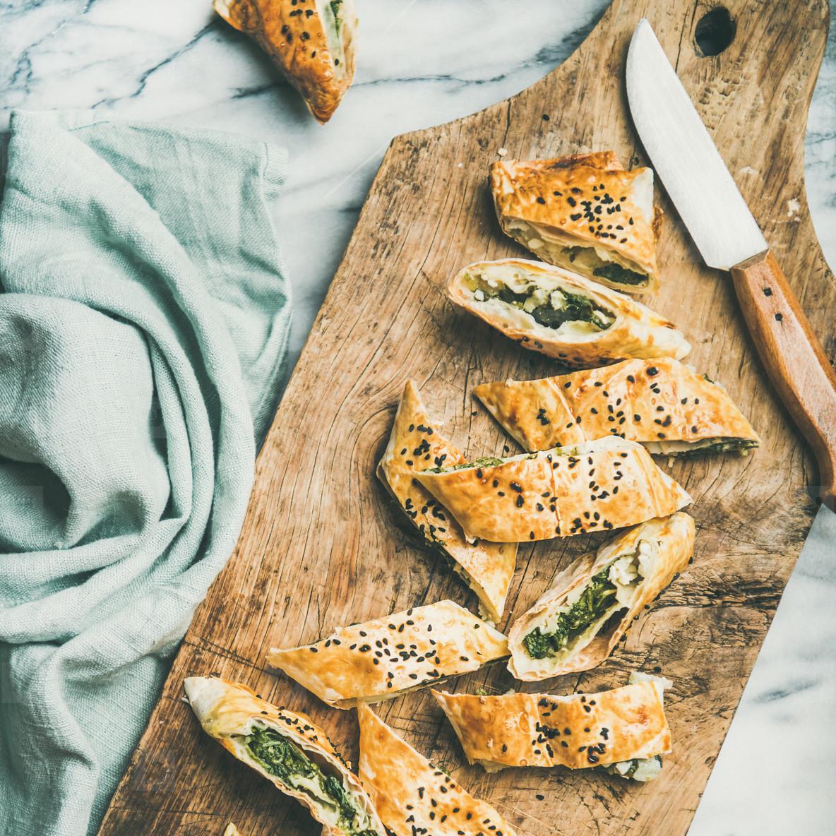 Freshly baked Turkish borek roll cut in slices  square crop