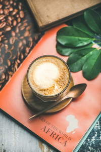 Cappuccino coffee in glass over table with bright magazine background