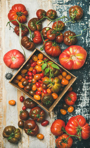 Flat  lay of fresh colorful tomatoes over rustic background