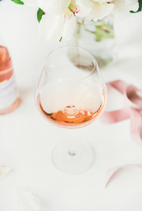 Rose wine in glass  pink ribbon  peony flowers