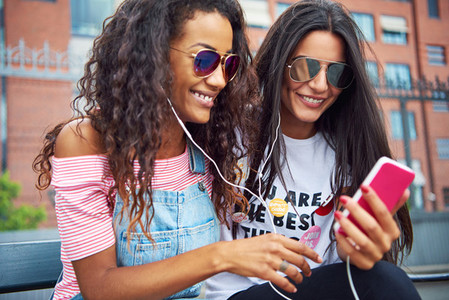 Young girlfriends sitting together outside streaming video on a smartphone