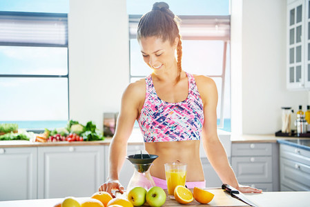 Happy sporty woman looking at juice extractor